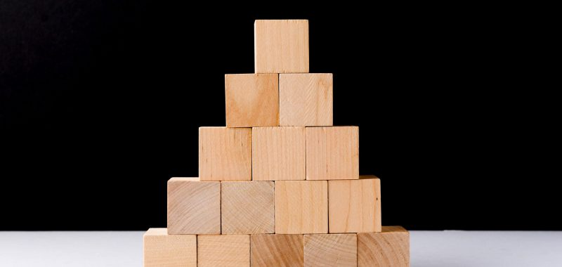 Stacking,Wooden,Cubes,On,Black,Background.,Business,Concept,On,Progress